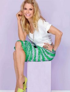 Julie Bowen with an amazing smile in a photo session, wearing a white shirt and a green skirt