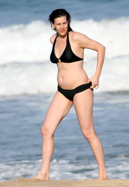 With her slim body and Dark brown hairtype without bra (cup size 36B) on the beach in bikini