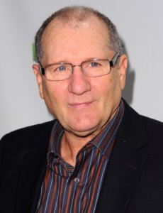 Ed O'Neill in a black jacket with a shirt with stripes