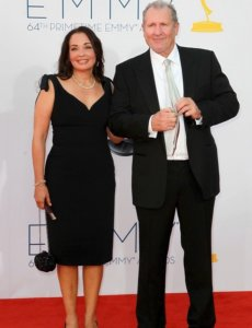 Ed O'Neill and his wife in a black suit at an Emmy award ceremony