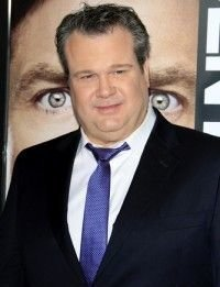Eric Stonestreet in a black suit with a blue tie