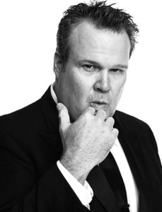 Great black and white photo of Eric Stonestreet in a suit with the hand in his chin