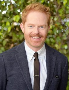 Jesse Tyler Ferguson smiling in a gray suit