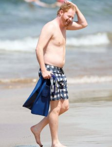Jesse Tyler Ferguson shirtless on the beach scratching his head