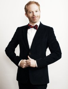 Jesse Tyler Ferguson body picture in a black suit and wearing a red bow tie