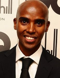 Mo Farah smiling in a black suit and tie