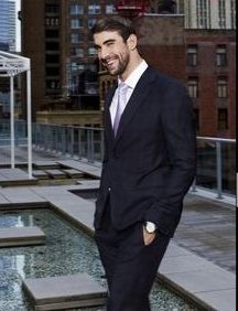 Michael Phelps full body image in a suit, smiling