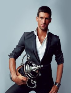 Novak Djokovic posing for a photo shot with a trophy in a grey suit and whit shirt