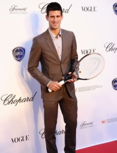 Novak Djokovic in a brown suit with a tennis racket in his hand