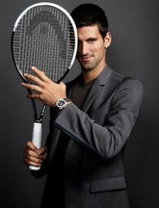 Novak Djokovic smiling in a suit and with a tennis racket