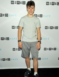 Nolan Gould looking great in a casual outfit: grey shorts and beige shirt