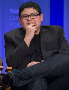 Rico Rodriguez seated looking puzzled in a black jacket and wearing glasses