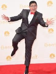 Rico Rodriguez in a black suit and bow tie in a funny position during an award cerimony