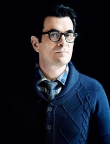 Ty Burrell with glasses in a blue shirt with a serious look
